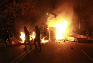 Estudantes chilenos passam em frente a cabine telefônica pegando fogo durante protesto em Santiago